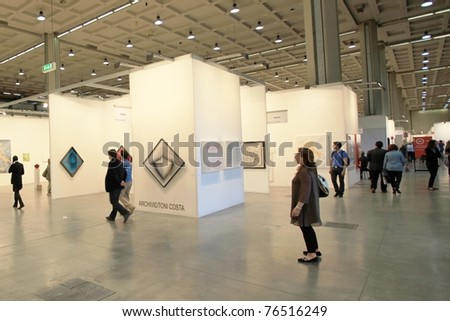 MILAN - APRIL 08: People look at paintings dedicated to Marilyn Monroe, Paul Newman and John Lennon at MiArt, international exhibition of modern and contemporary art on April 08, 2011 in Milan