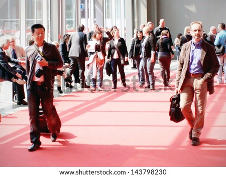 MILAN - APRIL 15: people walk while visiting Salone del Mobile, international furnishing accessories exhibition April 15, 2010 in Milan, Italy. - stock photo