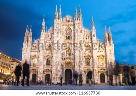 Milan Cathedral (Duomo di Milano) is the gothic cathedral church of Milan, Italy. Shot in the dusk from the square ful of people. - stock photo