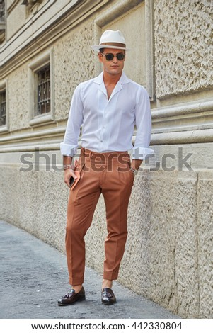 MILAN - FEBRUARY 19: Elegant man poses for photographers with brown trousers and Borsalino hat before Salvatore Ferragamo fashion show, Milan Men's Fashion Week street style on June 19, 2016 in Milan. - stock photo