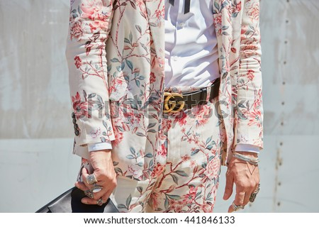 MILAN - FEBRUARY 20: Man poses for photographers with pink Gucci floral suit and belt before Gucci fashion show, Milan Men's Fashion Week street style on June 20, 2016 in Milan.