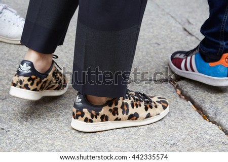 MILAN - FEBRUARY 19: Man poses for photographers with Stan Smith Adidas shoes before Boglioli fashion show, Milan Men's Fashion Week street style on June 19, 2016 in Milan. - stock photo