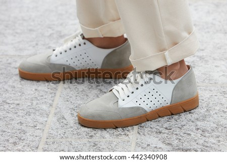 MILAN - FEBRUARY 18: Man poses for photographers with white and gray Loewe shoes before Canali fashion show, Milan Men's Fashion Week street style on June 18, 2016 in Milan. - stock photo