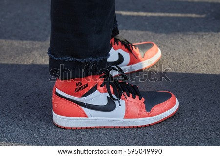MILAN - FEBRUARY 27: Man with orange Nike Air Jordan shoes before Giorgio  Armani fashion