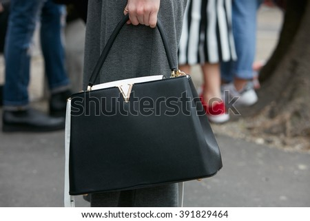 MILAN - FEBRUARY 26: Woman poses for photographers with black and white Louis Vuitton bag before Emporio Armani fashion show, Milan Fashion Week Day 3 street style on February 26, 2016 in Milan. - stock photo