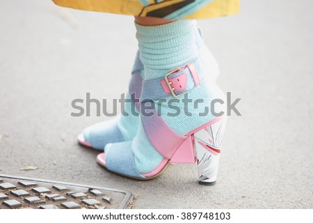 MILAN - FEBRUARY 25: Woman poses for photographers with blue and pink shoes and socks before Fendi fashion show, Milan Fashion Week Day 2 street style on February 25, 2016 in Milan.