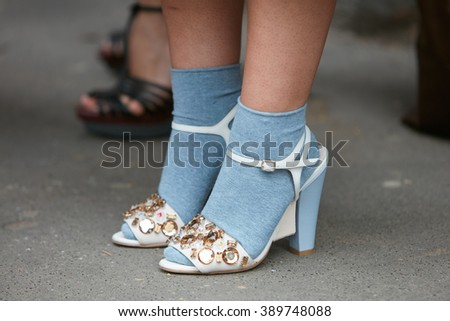 MILAN - FEBRUARY 25: Woman poses for photographers with blue socks and white shoes with gems before Fendi fashion show, Milan Fashion Week Day 2 street style on February 25, 2016 in Milan. - stock photo