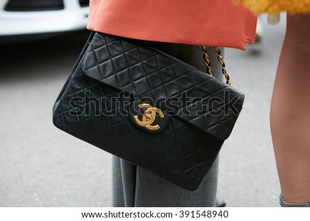 MILAN - FEBRUARY 26: Woman poses for photographers with Chanel bag with golden logo before Etro and Iceberg fashion show, Milan Fashion Week Day 3 street style on February 26, 2016 in Milan.