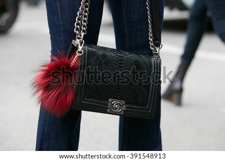 MILAN - FEBRUARY 26: Woman poses for photographers with Chanel black snake bag with Fendi fur accessory before Etro fashion show, Milan Fashion Week Day 3 street style on February 26, 2016 in Milan.