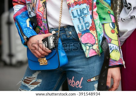 MILAN - FEBRUARY 26: Woman poses for photographers with colorful designed jacket and blue bag before Etro and Iceberg fashion show, Milan Fashion Week Day 3 street style on February 26, 2016 in Milan. - stock photo