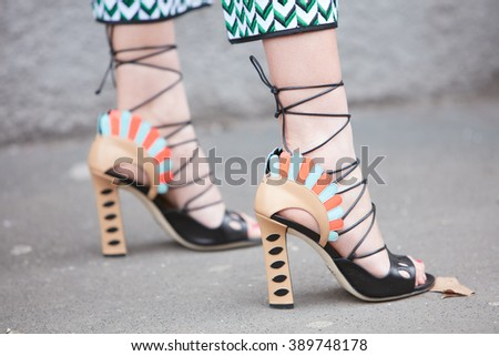 MILAN - FEBRUARY 25: Woman poses for photographers with Fendi high heel shoes before Fendi fashion show, Milan Fashion Week Day 2 street style on February 25, 2016 in Milan. - stock photo