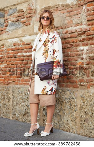MILAN - FEBRUARY 24: Woman poses for photographers with floral coat and Saint Laurent bag before Blugirl fashion show, Milan Fashion Week Day 1 street style on February 24, 2016 in Milan. - stock photo