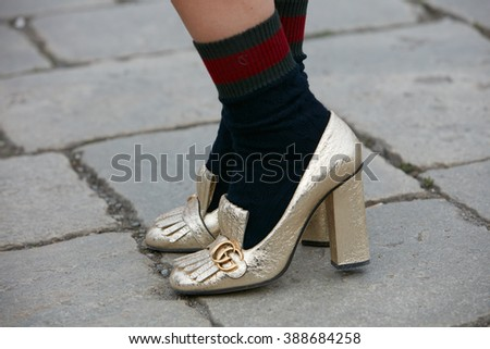 MILAN - FEBRUARY 24: Woman poses for photographers with golden Gucci shoes and socks before Gucci fashion show, Milan Fashion Week Day 1 street style on February 24, 2016 in Milan.