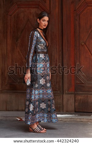 MILAN - FEBRUARY 19: Woman poses for photographers with long dress before Salvatore Ferragamo fashion show, Milan Men's Fashion Week street style on June 19, 2016 in Milan. - stock photo