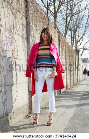 MILAN - FEBRUARY 25: Woman poses for photographers with pink coat and colorful striped sweater before Emilio Pucci fashion show, Milan Fashion Week Day 2 street style on February 25, 2016 in Milan. - stock photo