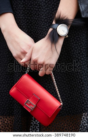 MILAN - FEBRUARY 25: Woman poses for photographers with red Fendi bag and black fur watch before Fendi fashion show, Milan Fashion Week Day 2 street style on February 25, 2016 in Milan.