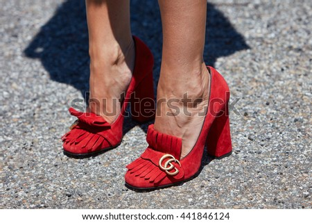 MILAN - FEBRUARY 20: Woman poses for photographers with red Gucci high heel shoes before Gucci fashion show, Milan Men's Fashion Week street style on June 20, 2016 in Milan.