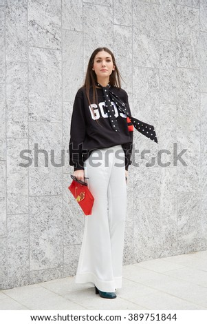 MILAN - FEBRUARY 25: Woman poses for photographers with red Loewe bag before Costume National fashion show, Milan Fashion Week Day 2 street style on February 25, 2016 in Milan. - stock photo