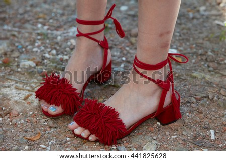 MILAN - FEBRUARY 20: Woman poses for photographers with red open shoes with fringes before Fendi fashion show, Milan Men's Fashion Week street style on June 20 2016 in Milan.