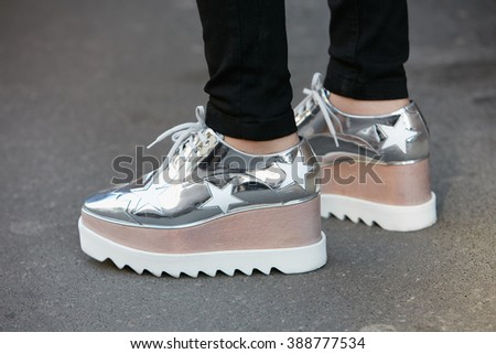 MILAN - FEBRUARY 24: Woman poses for photographers with silver shoes with stars before Blugirl fashion show, Milan Fashion Week Day 1 street style on February 24, 2016 in Milan. - stock photo