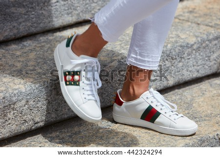 MILAN - FEBRUARY 19: Woman poses for photographers with white Gucci shoes before Salvatore Ferragamo fashion show, Milan Men's Fashion Week street style on June 19, 2016 in Milan.