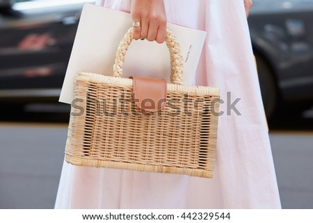 MILAN - FEBRUARY 19: Woman poses for photographers with wicker bag and pink dress before Salvatore Ferragamo fashion show, Milan Men's Fashion Week street style on June 19, 2016 in Milan. - stock photo