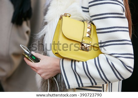 MILAN - FEBRUARY 25: Woman poses for photographers with yellow Valentino bag with studs before Cristiano Burani fashion show, Milan Fashion Week Day 2 street style on February 25, 2016 in Milan.