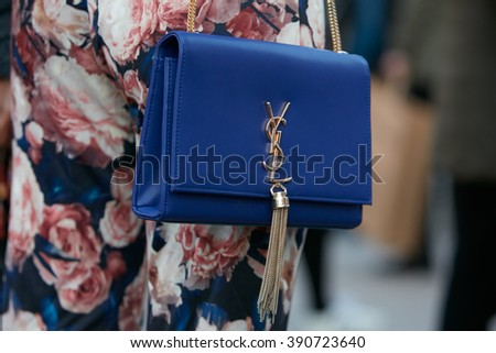 MILAN - FEBRUARY 25: Woman poses for photographers with Yves Saint Laurent blue bag before Cristiano Burani fashion show, Milan Fashion Week Day 2 street style on February 25, 2016 in Milan.