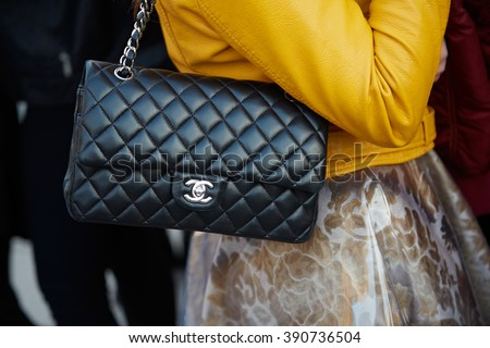 MILAN - FEBRUARY 25: Woman poses with black leather Chanel bag and yellow jacket before Cristiano Burani fashion show, Milan Fashion Week Day 2 street style on February 25, 2016 in Milan. - stock photo