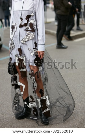 MILAN - FEBRUARY 26: Woman poses with white and transparent dress with tribal designs before Emporio Armani fashion show, Milan Fashion Week Day 3 street style on February 26, 2016 in Milan.
