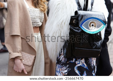 MILAN - FEBRUARY 25: Woman waiting with eye backpack before Genny show Milan Fashion Week Day 1, Fall/Winter 2015/2016 street style day 1, on February 25, 2015 in Milan. - stock photo