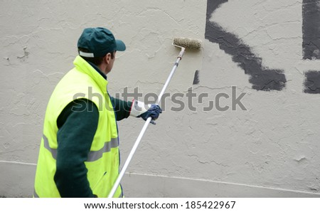 MILAN, ITALY-APRIL 04, 2014: Clean worker with paint roller, removes graffiti signs from a wall of a private building, in Milan.