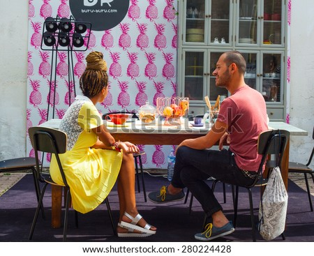 MILAN, ITALY - APRIL 16: Couple of friends enjoying a conversation in the kitchen room at Buru-buru stand in theTortona space location during Milan Design week on April 16, 2015 - stock photo