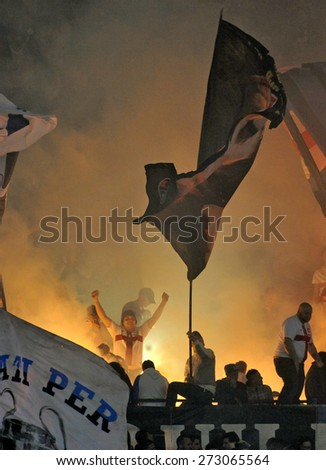MILAN, ITALY-APRIL 19, 2015: FC Internazionale soccer fans waving flags and firing up smoke bombs, at the san siro soccer stadium, in Milan. - stock photo