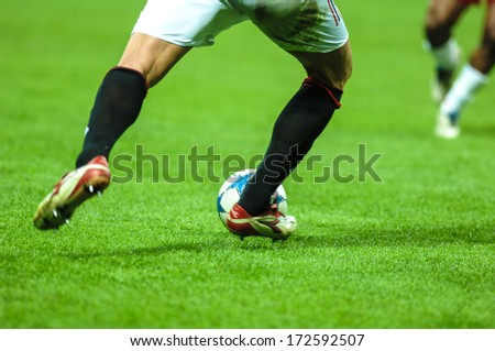 MILAN, ITALY - APRIL 06: Italian professional Serie A soccer match in Milan April 06, 2006. A football player close up kicking the ball with the green pitch on the background.