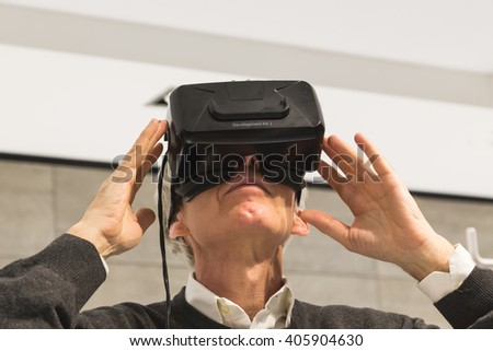 MILAN, ITALY - APRIL 13: Man wears virtual reality headset at Fuorisalone, set of events distributed in different areas of the town during Milan Design Week on APRIL 13, 2016 in Milan. - stock photo