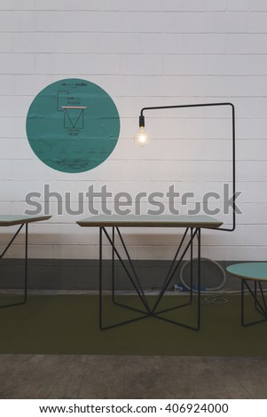 MILAN, ITALY - APRIL 16: Table and lamp on display at Fuorisalone, set of events distributed in different areas of the town during Milan Design Week on APRIL 16, 2016 in Milan. - stock photo