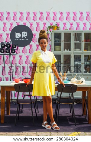 MILAN, ITALY - APRIL 16: Young girl next to the table in the kitchen. Buru-buru stand in the Tortona space location during Milan Design week on April 16, 2015 - stock photo