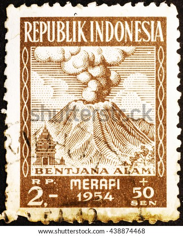 Milan, Italy - December 16, 2014: Erupting volcano on old indonesian postage stamp