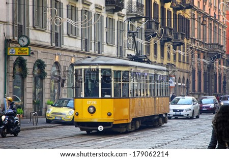 MILAN, ITALY - DECEMBER 31, 2010: Old traditional tram (ATM Class 1500) on the street of Milan. Milan tramway network operation since 1881, and now network is about 115 km long - stock photo