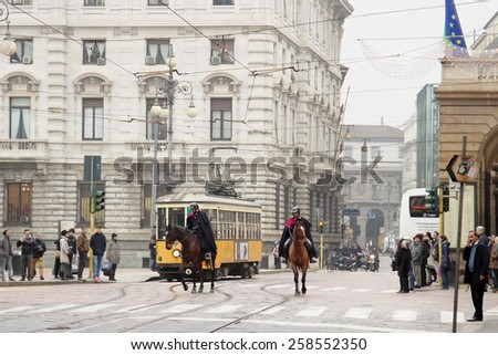 MILAN, ITALY - DECEMBER 24 2014: Police riding horses near the trolley on  DECEMBER 24, 2014 in Milan. - stock photo