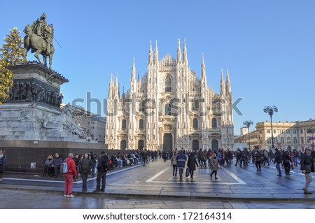 MILAN, ITALY - December 27, 2013 - Tourists in Piazza Duomo in front of the Duomo di Milano gothic cathedral church Milan Italy - stock photo
