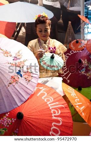 MILAN, ITALY - FEBRUARY 17: A Thai woman paints on umbrellas at BIT International Tourism Exchange on february 17, 2012 in Milan, Italy. - stock photo