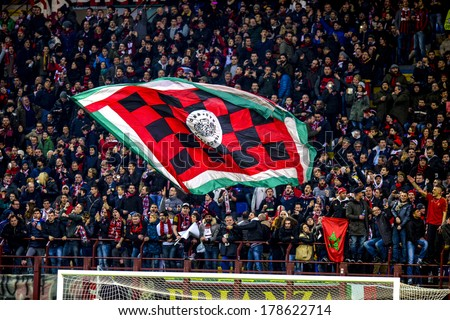 MILAN, ITALY-FEBRUARY 19, 2014: AC Milan fans waving a team flag during a soccer UEFA Champions League match AC Milan vs Athletic Madrid, at  the San Siro stadium. - stock photo