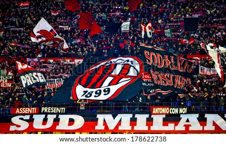 MILAN, ITALY-FEBRUARY 19, 2014: AC Milan fans waving a team flags during a soccer UEFA Champions League match AC Milan vs Athletic Madrid, at  the San Siro stadium. - stock photo