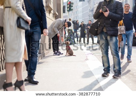 MILAN, ITALY - FEBRUARY 25, 2016: Fashionable man and his dog on a leash attending models and vips in the streets during Milan Fashion Week Women Fall/Winter 2016/2017
