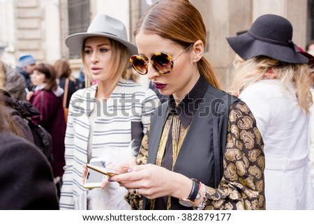 MILAN, ITALY - FEBRUARY 25, 2016: Fashionable woman attending models and vips using smartphone in the streets during Milan Fashion Week Women Fall/Winter 2016/2017