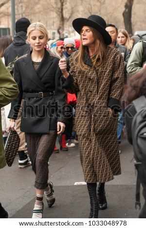 MILAN, ITALY - FEBRUARY 22, 2018: Stylish Anna dello Russo posing in FENDI trench coat outside FENDI during Milan Fashion Week Fall/Winter 2018/19 on February 22, 2018 in Milan, Italy.