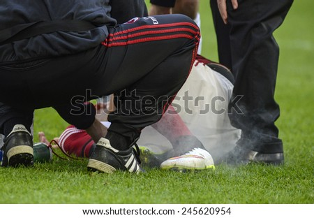 MILAN, ITALY-JANUARY 18, 2015: soccer player injured receive first aid at the san siro stadium, at the end of the italian serie A soccer match AC Milan vs Atalanta, in Milan. - stock photo
