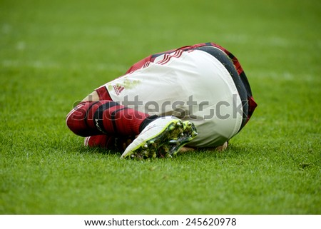 MILAN, ITALY-JANUARY 18, 2015: soccer player laying on the grass for injury at the san siro stadium, at the end of the italian serie A soccer match AC Milan vs Atalanta, in Milan. - stock photo